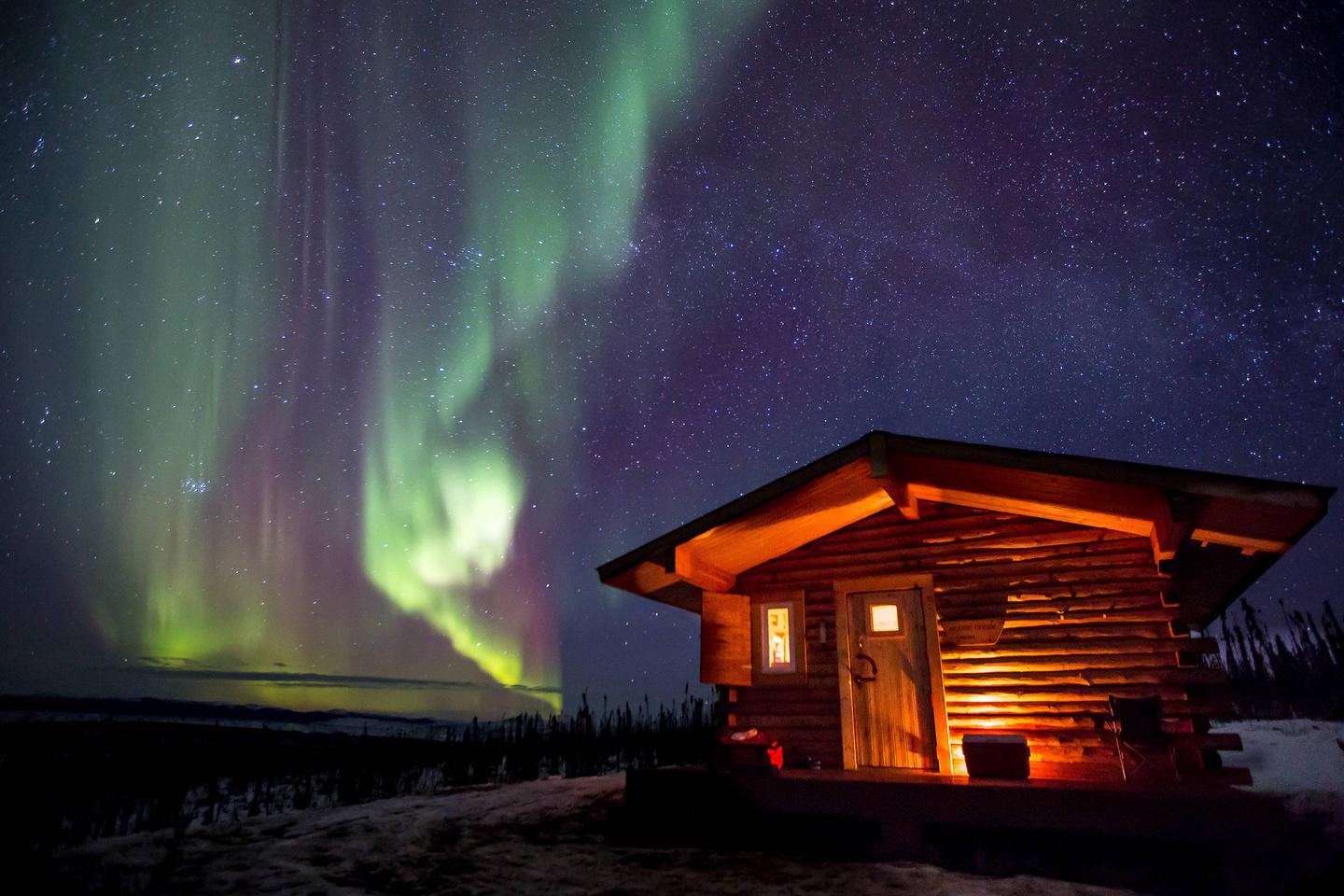A cabin beneath a starry sky with northern lights.Northern lights dance against a starry sky at Moose Creek Cabin.
