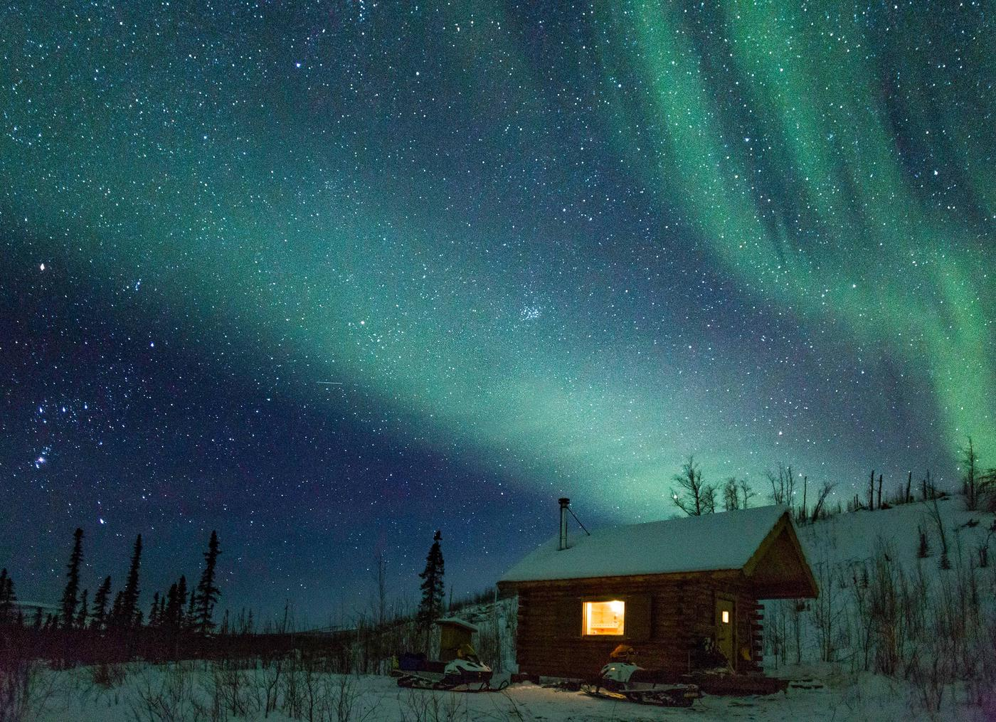 A cabin next to a low hill beneath northern lightsNorthern lights at Wolf Run Cabin.