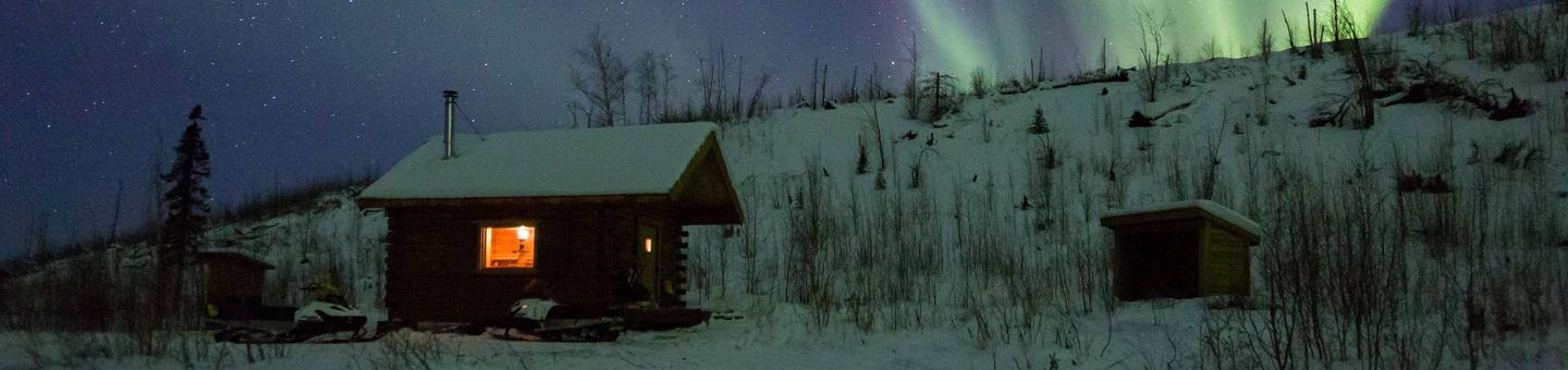 Cabin in front a hill under a night sky with northern lights.Wolf Run Cabin