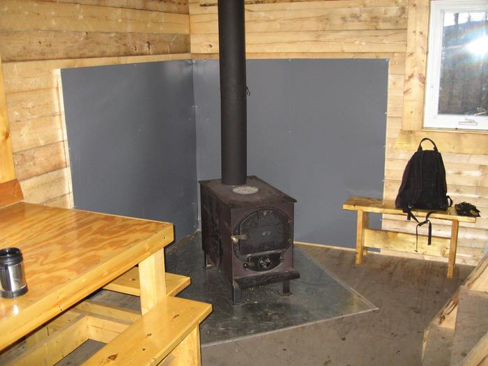 A woodstove, table, and bench in a log cabinWoodstove and table and Wolf Run Cabin