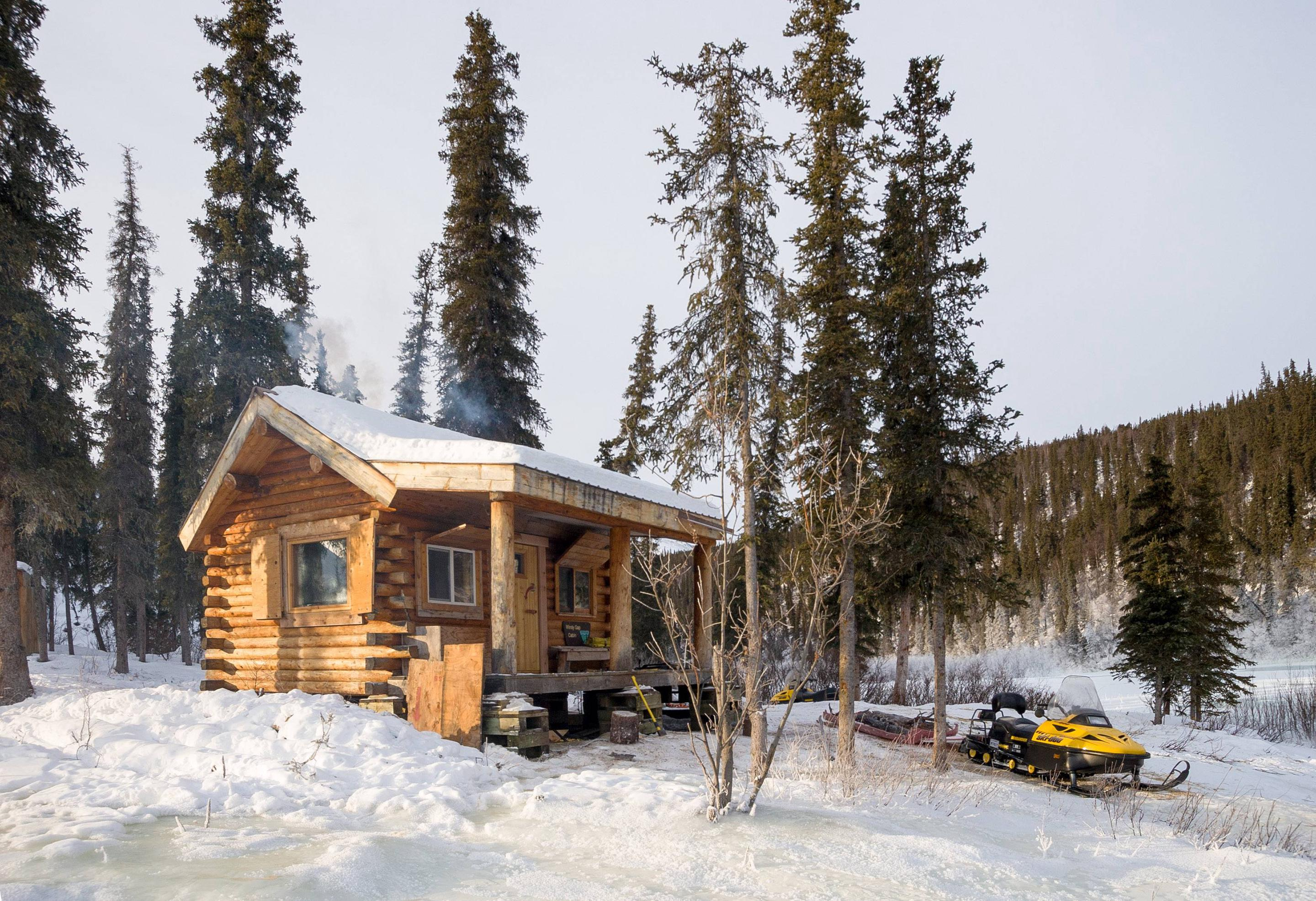 A cabin with a yellow snowmobile parked in frontWindy Gap cabin sits on a knoll above Fossil Creek.