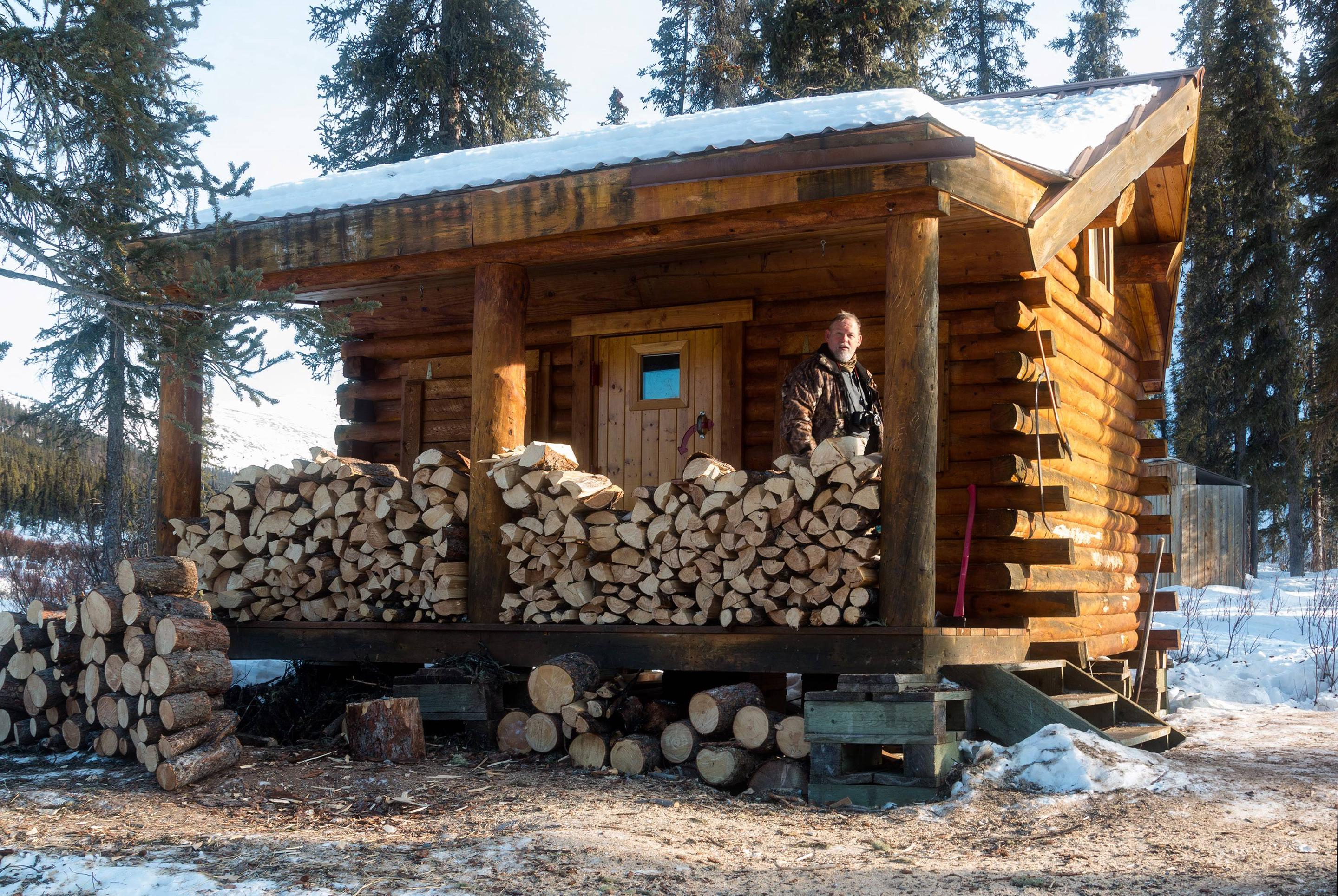 Log cabin with firewood piled on the front deckFront of Windy Gap Cabin piled high with firewood.