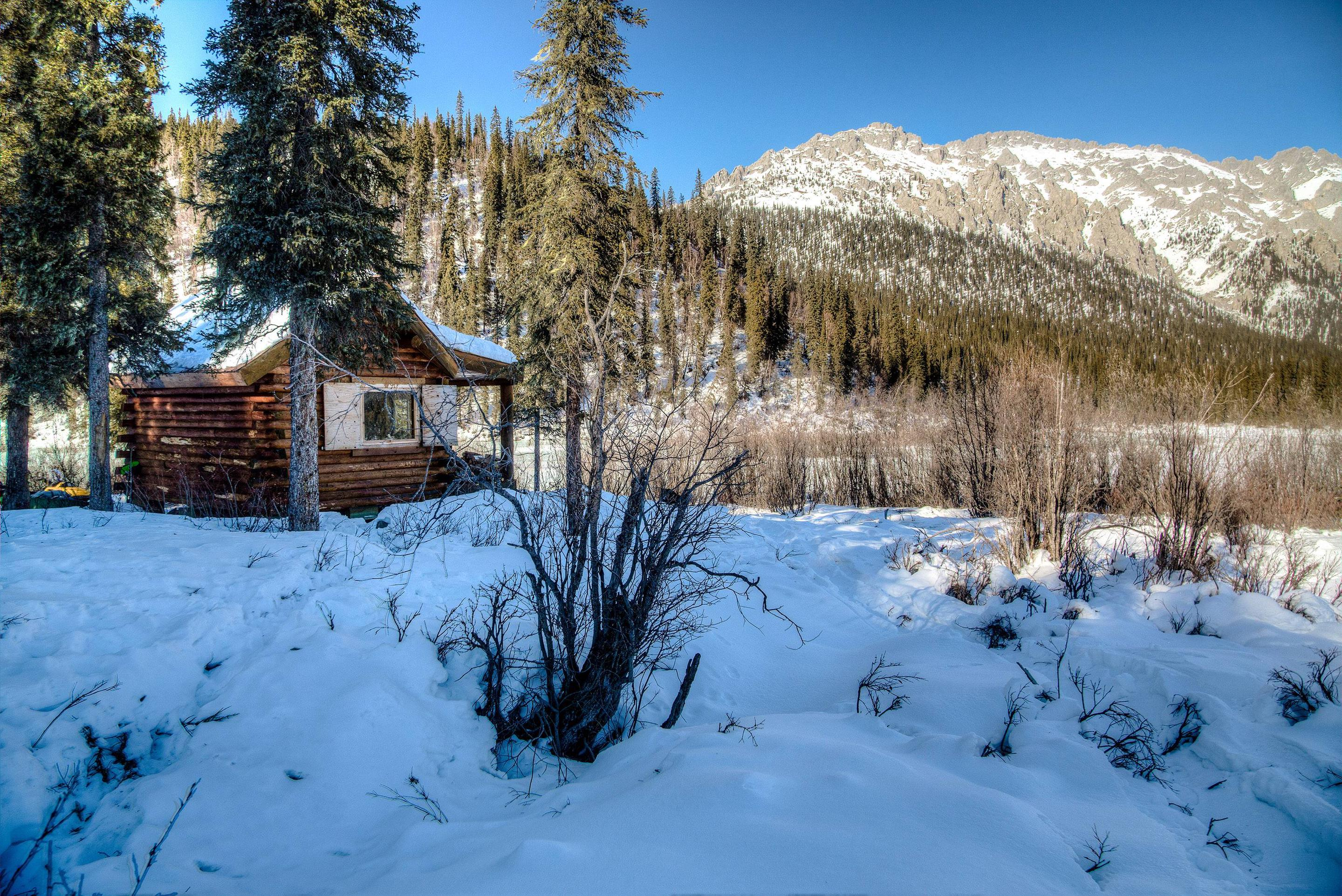 A cabin surrounded by snow in front of a forested and rocky ridgeWindy Gap Cabin and view of limestone ridge