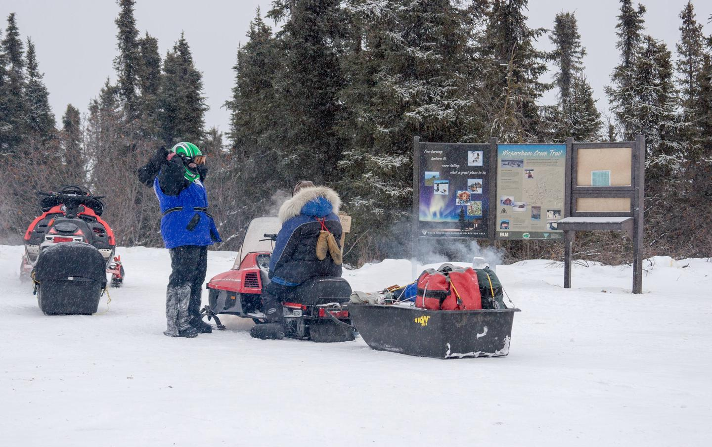 Two snowmobilers wait next to an information kiosk.White Mountains visitors prepare to depart Wickersham Dome Trailhead.