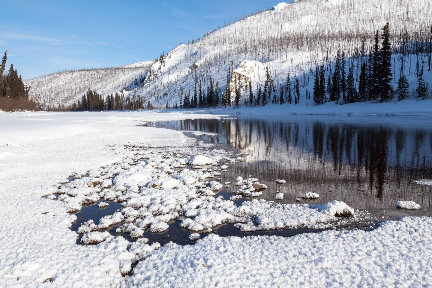 An open pool in a frozen river in snow-covered mountainsA spring keeps this section of Beaver Creek Wild and Scenic River from freezing despite frigid winter temperatures in the White Mountains.