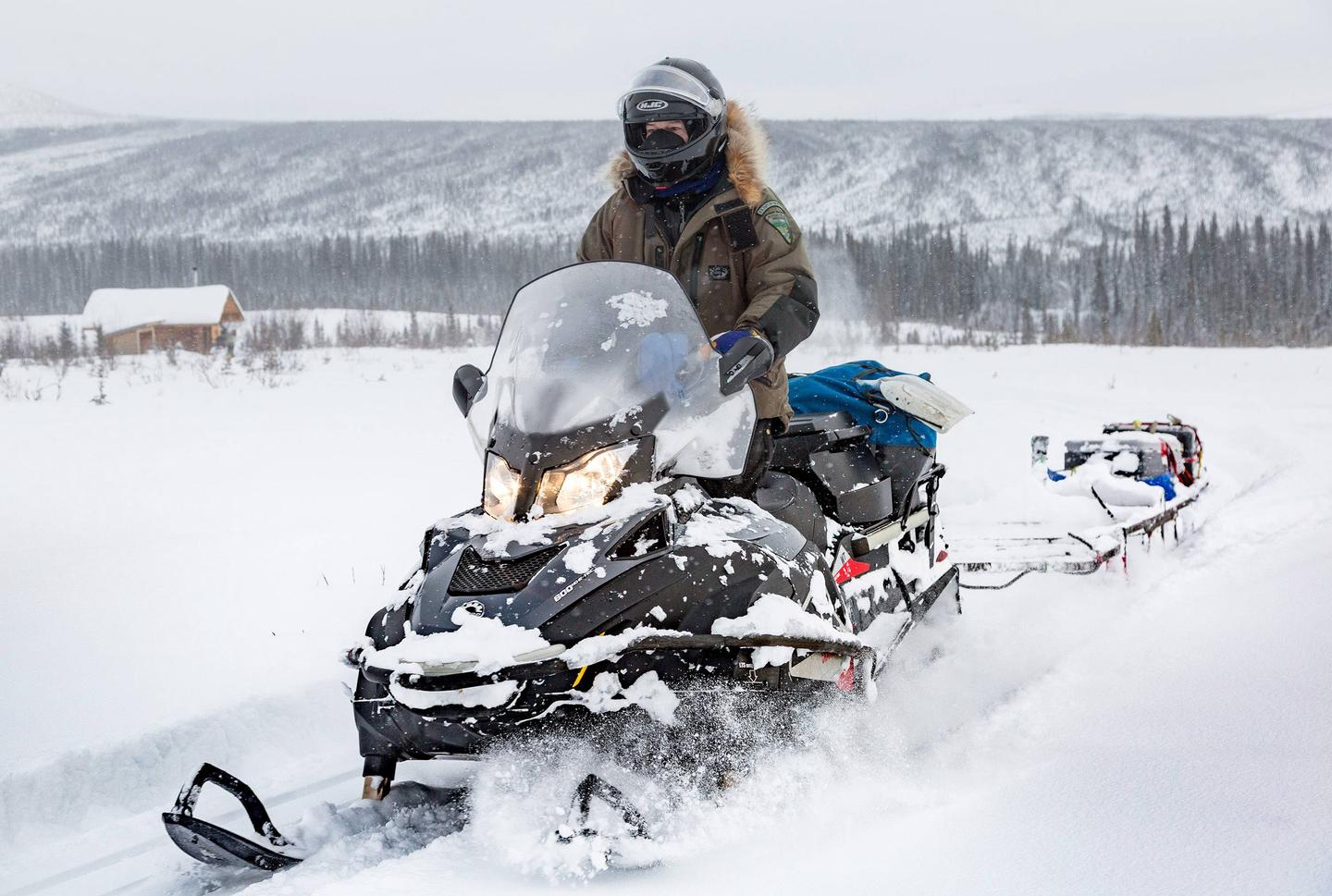 A snowmobiler rides past a log cabin The Bureau of Land Management grooms White Mountains trails throughout the winter, but visitors should still be prepared for the unexpected, including fresh snow, drifts, and cold temperatures.