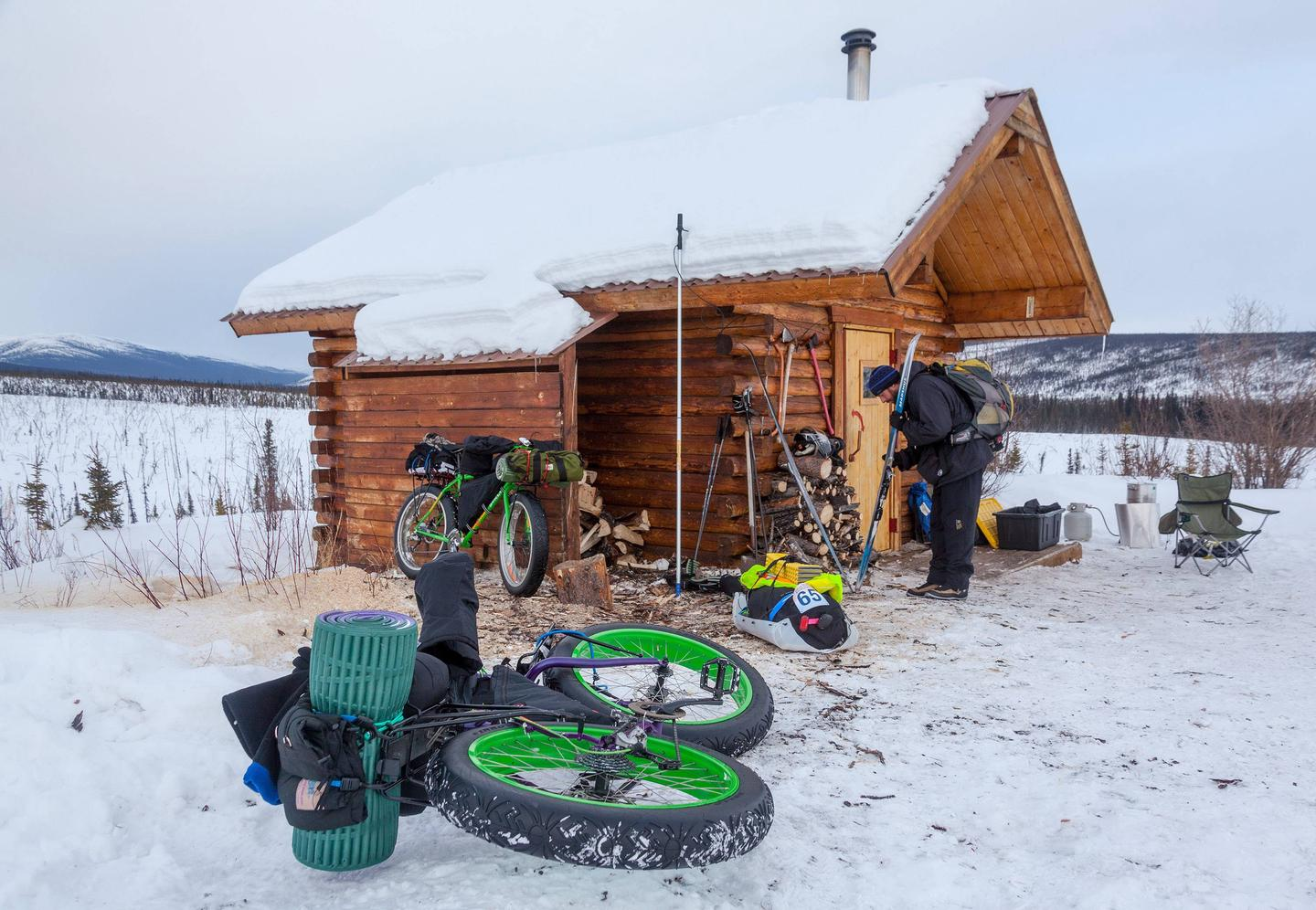 A man works on his skis next to parked bicycles at a log cabin.Bicyclists and skiers find cozy lodging at Cache Mountain Cabin.