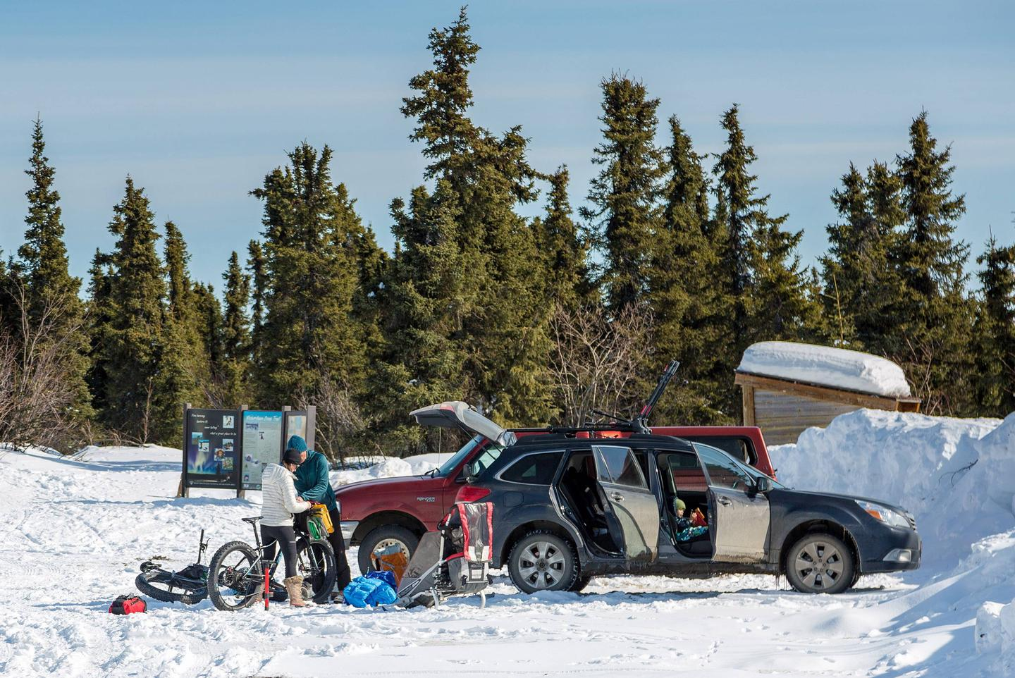 A family prepares camping gear and bicycles next to a car.Wickersham Dome Trailhead on the Elliott Highway is the busiest access point for trips into the White Mountains National Recreation Area.