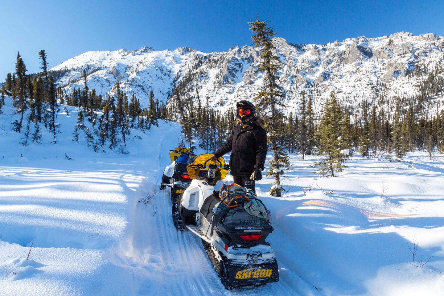 A man stands next to two snowmobiles in front of a rocky ridge.A snowmachine rider stops to enjoy the scenery along the Fossil Creek Trail in the White Mountains National Recreation Area.