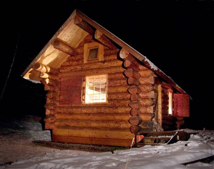 A log cabin at nightFred Blixt Cabin in winter offers a cozy, road-accessible getaway.