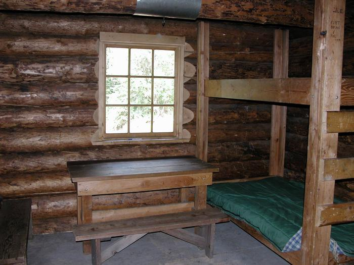 Interior of a log cabinTable, benches, and bunks in Fred Blixt Cabin.