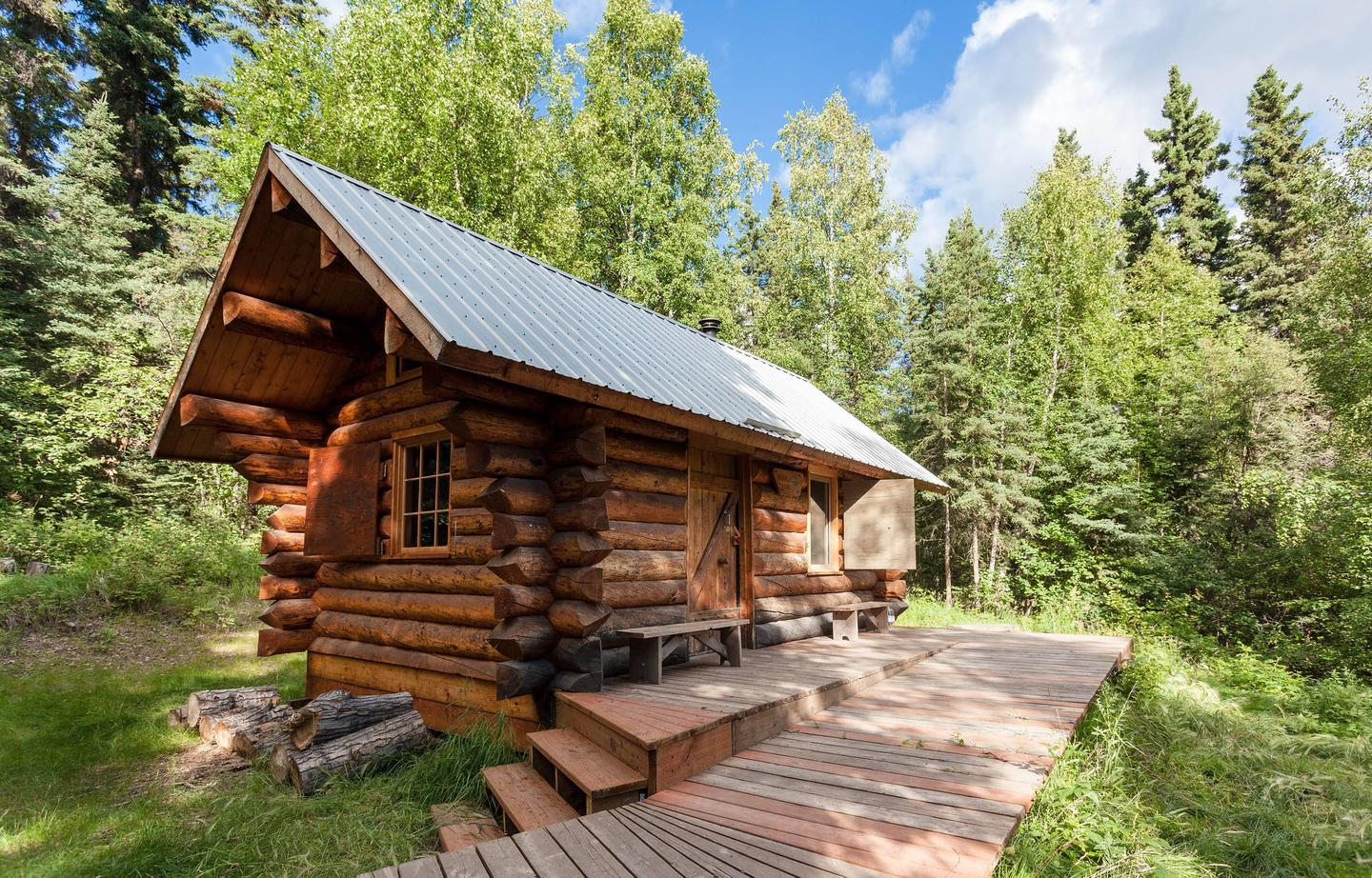 A log cabin sits in a forest of spruce and hardwood treesFred Blixt Cabin in summer.