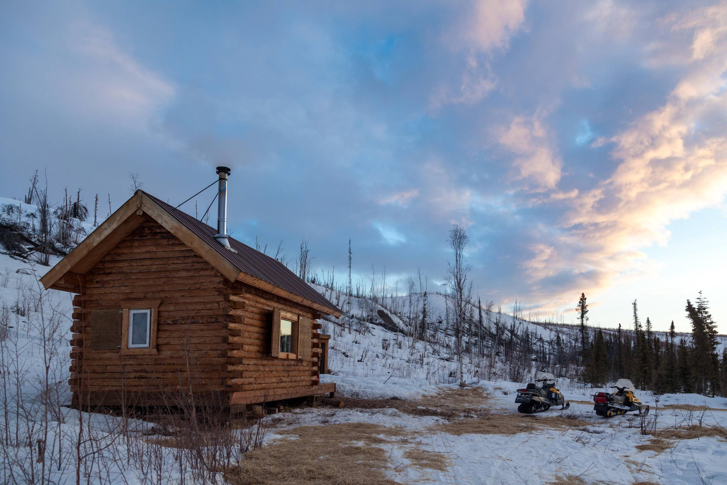 A log cabin under a partly cloudy skyEvening view of Wolf Run Cabin