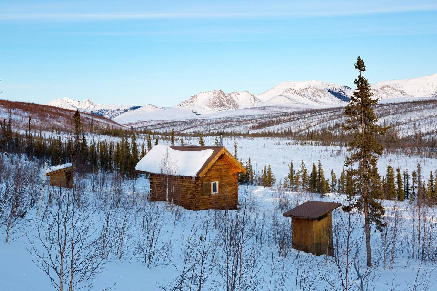 A cabin, shed, and outhouse face a broad, snow-covered valley and mountains.Wolf Run Cabin sits on a low ridge above Windy Creek with views of prominent White Mountains peaks.