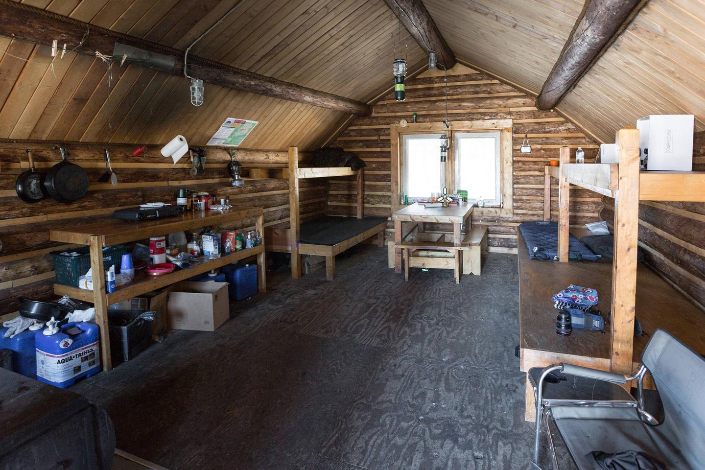 Bunks, table, benches and kitchen counter inside a log cabinSpacious interior of Richard's Cabin