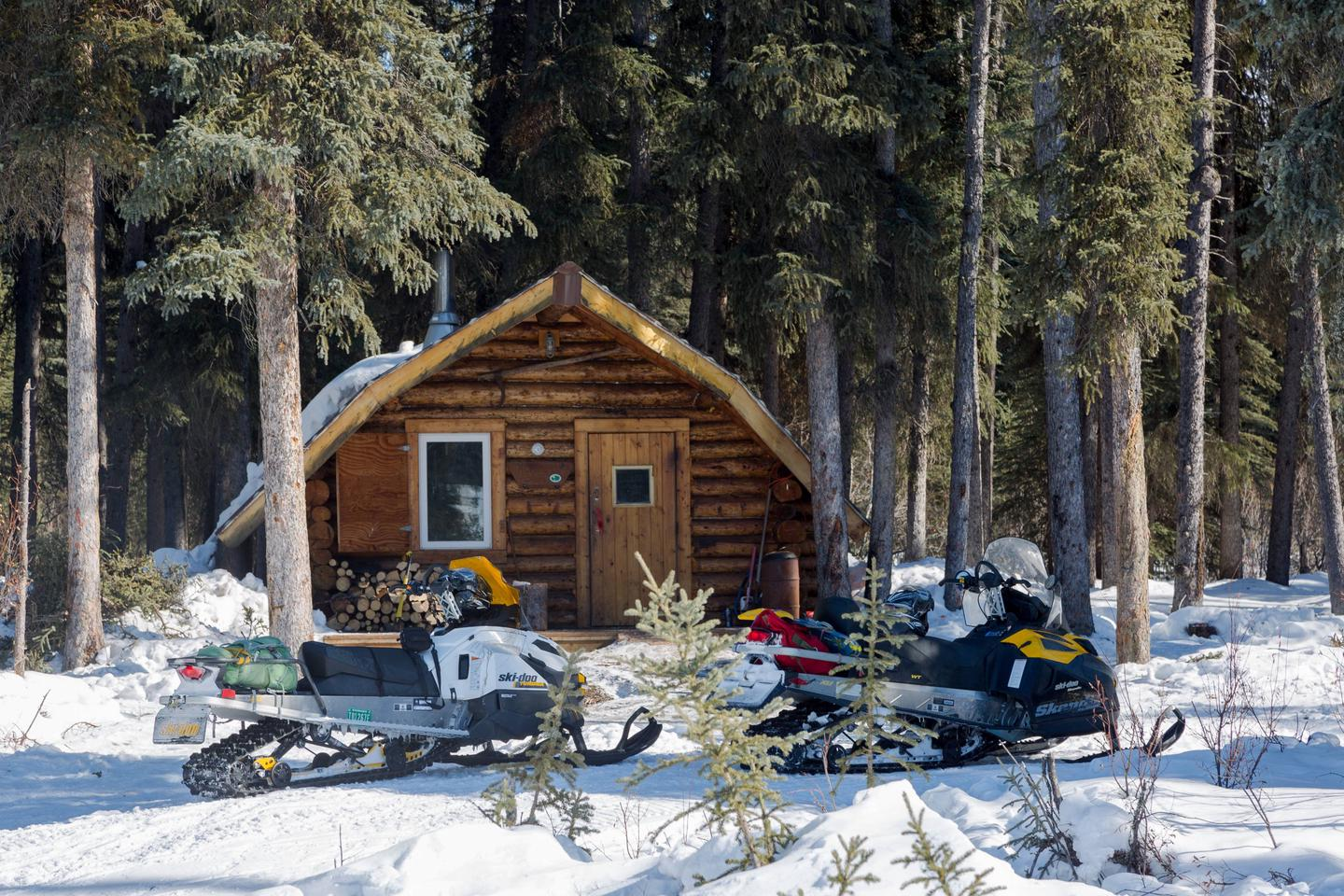Two snowmobiles are parked in front of a log cabin.Richard's Cabin