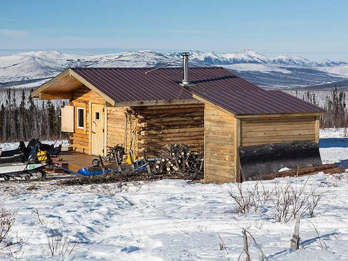 A log cabin and woodshed with mountains in the backgroundCrowberry Cabin