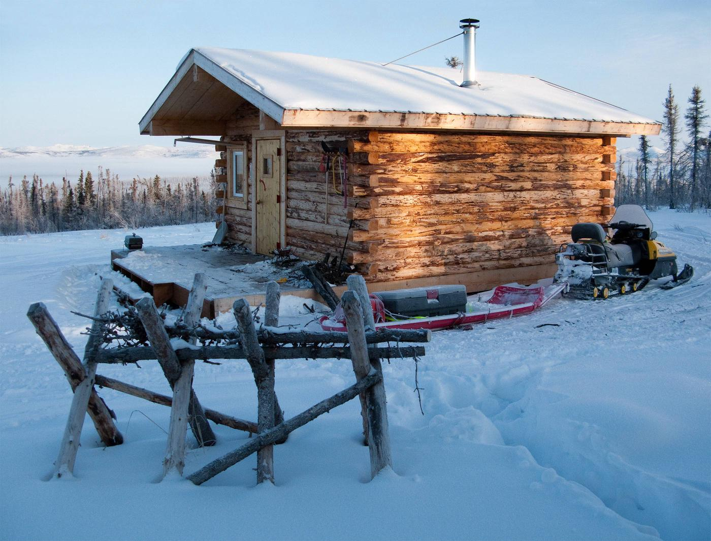 Log cabin and snowmobile in winterCrowberry Cabin