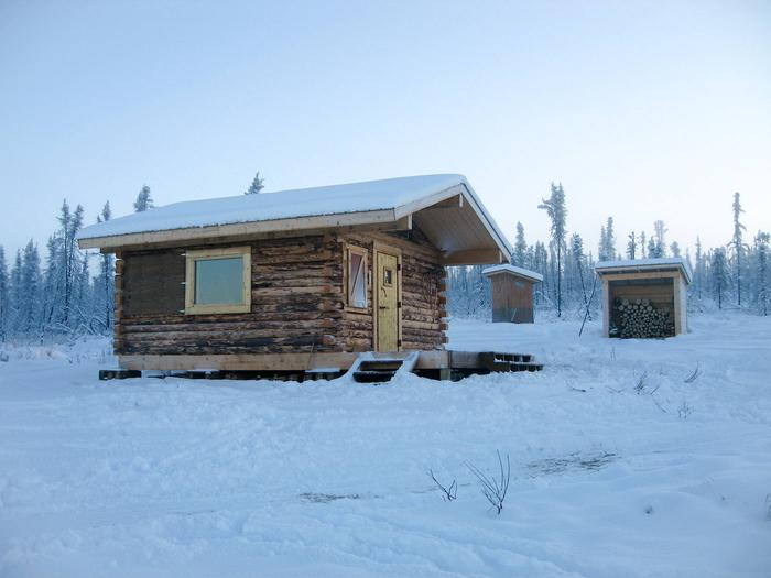 Log cabin, outhouse, and woodshed surrounded by snow.View of Crowberry Cabin from the access trail.