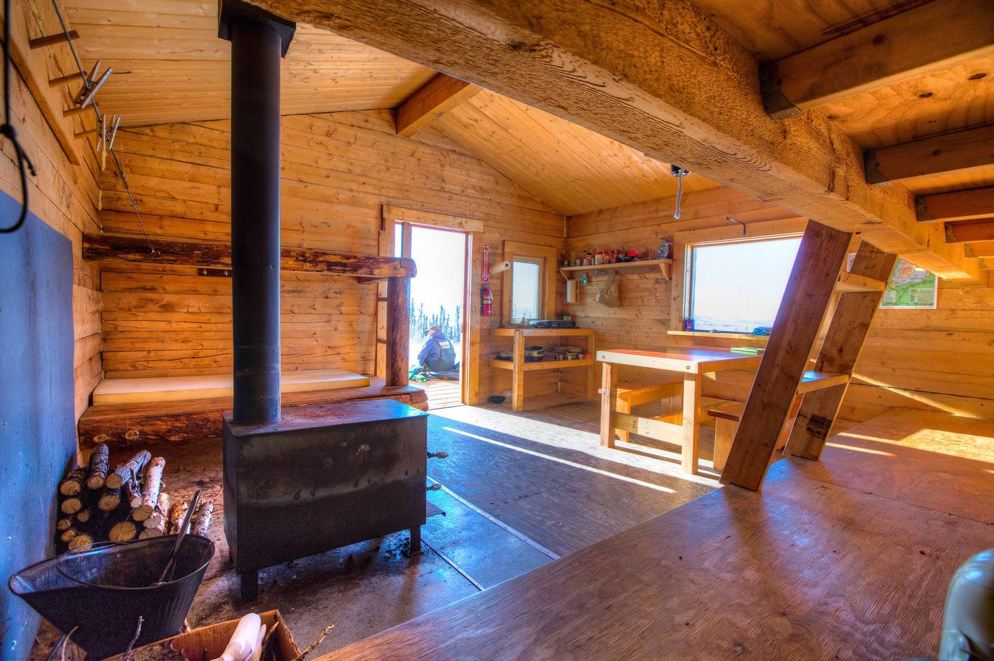 Inside of a log cabin with bunks and woodstoveInterior of Crowberry Cabin