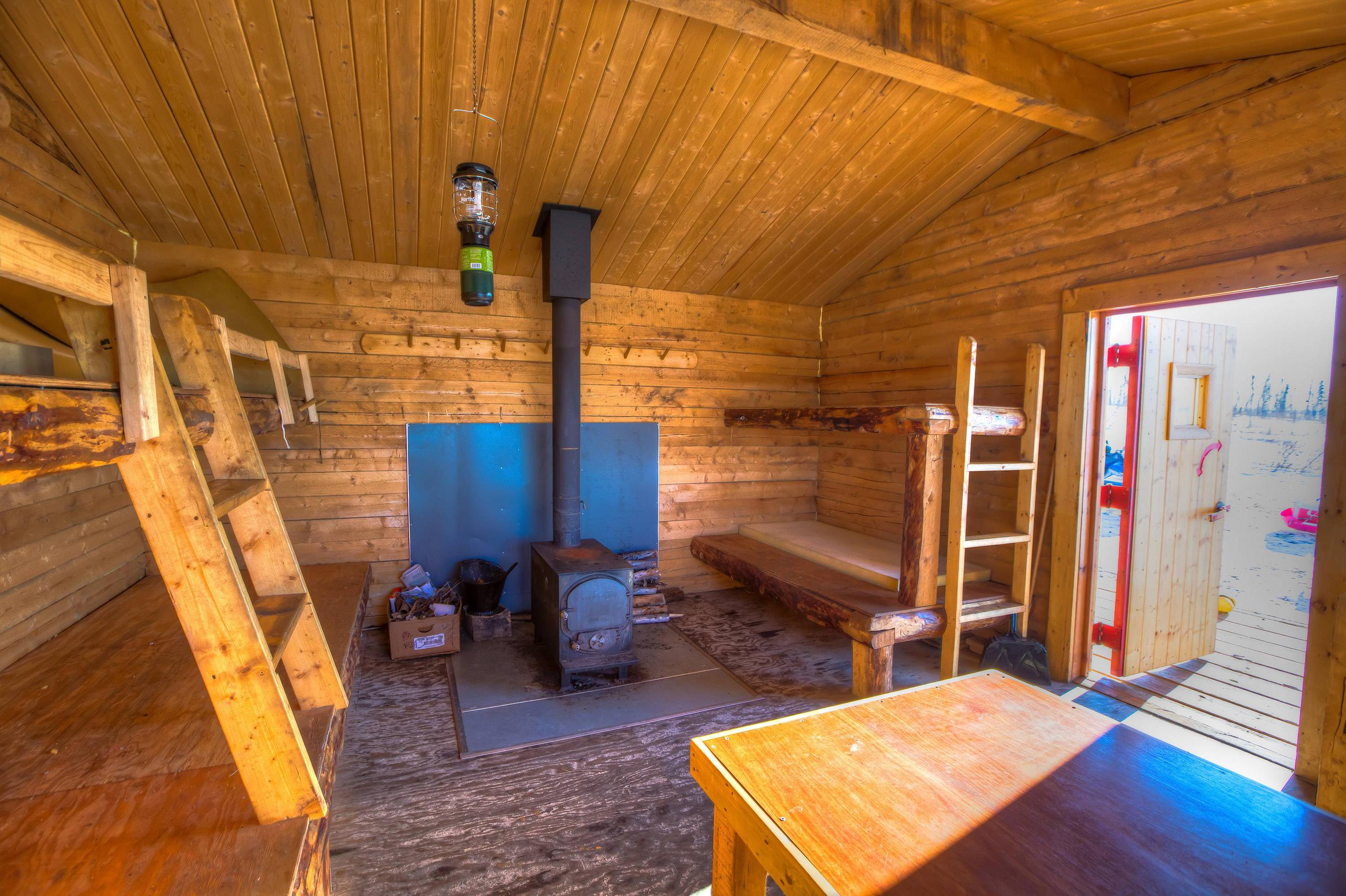 Bunks and woodstove in a log cabinBunks, table, and woodstove in Crowberry Cabin.