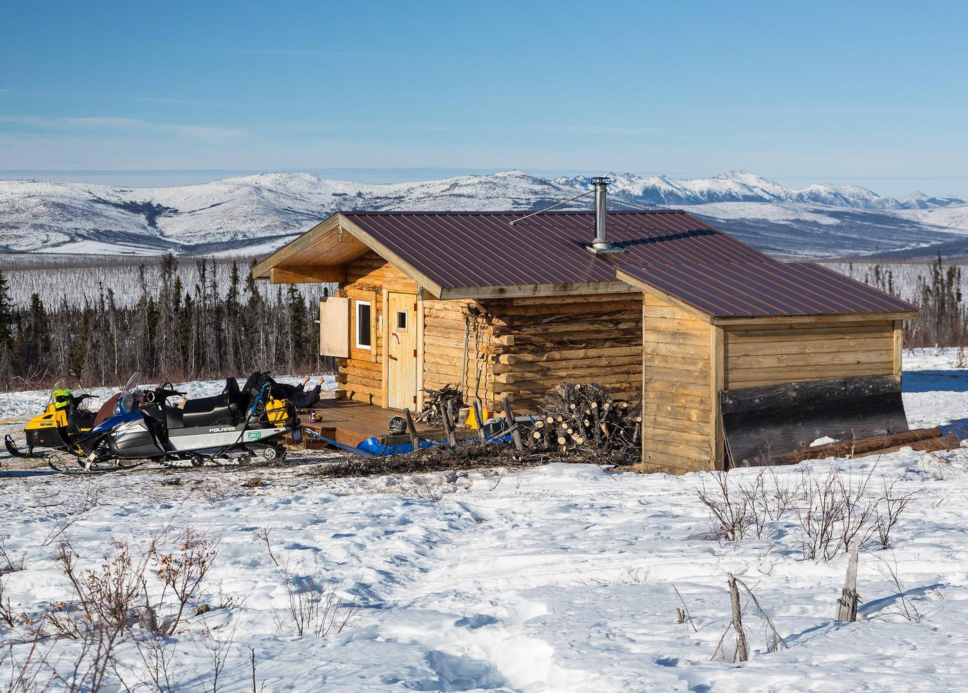 Winter view of a log cabin and woodshed with mountains in the distanceCrowberry Cabin has expansive views of the Beaver Creek valley and White Mountains.