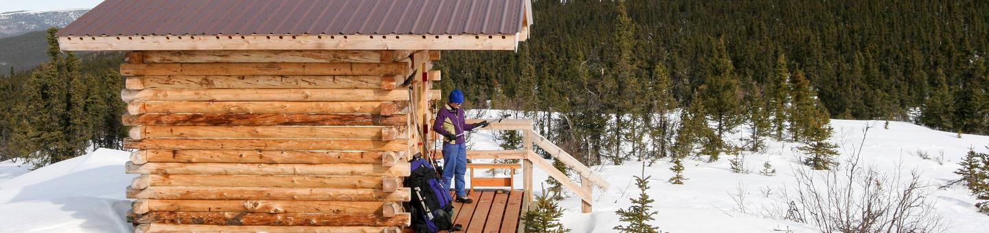 A log cabin on a snowy hilltopSummit Trail Shelter in winter