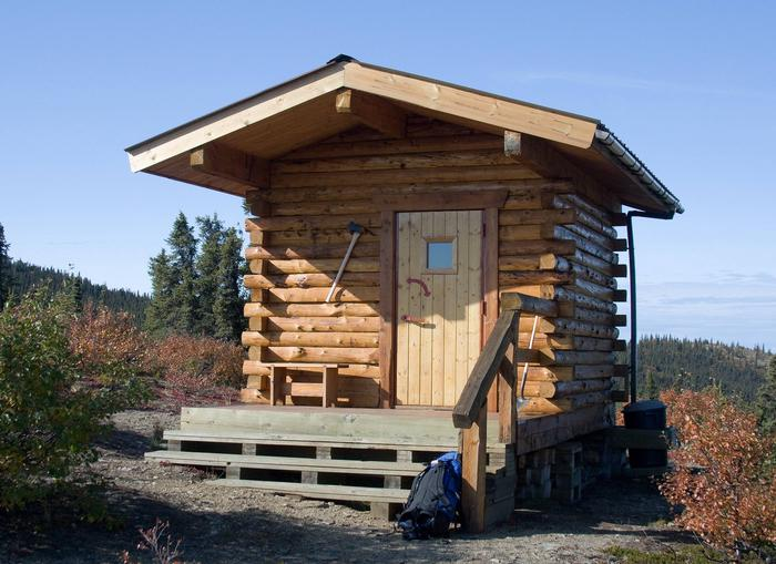 Front side of small log cabinSummit Trail Shelter in the fall