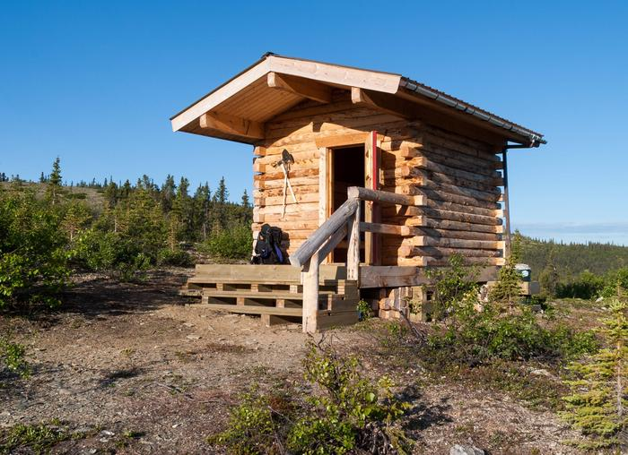 A small cabin with an open front doorSummit Trail Shelter in summer.