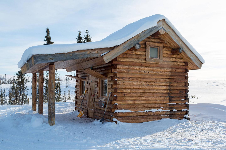 Log cabin with front porch in winterColorado Creek Cabin