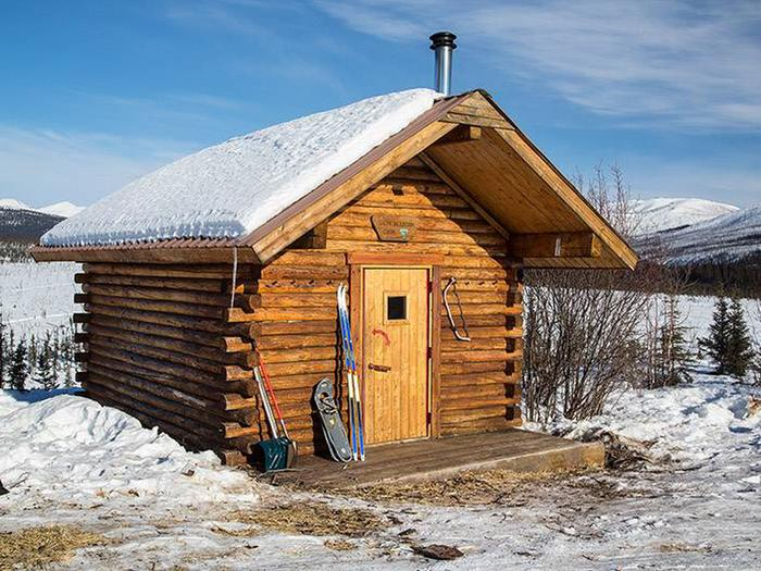 Log cabin with skis and snowshoes leaning against front wallCache Mountain Cabin