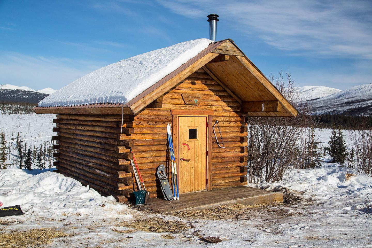 Log cabin with snowshoes and skis leaning on front wallFront of Cache Mountain Cabin