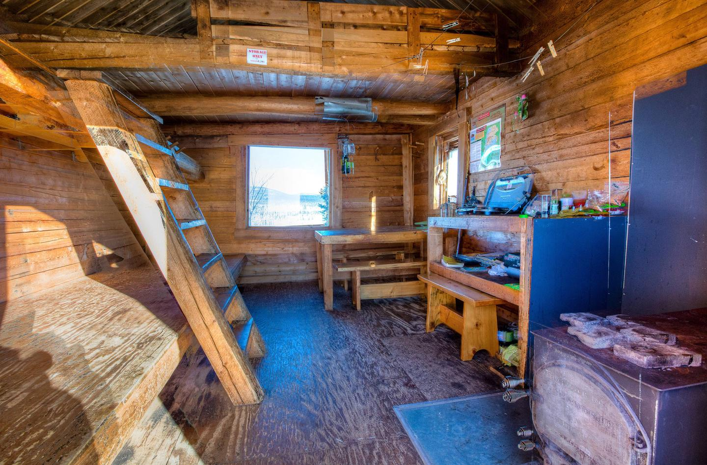 Interior view of small log cabinInterior of Cache Mountain Cabin with bunks, woodstove, and eating area