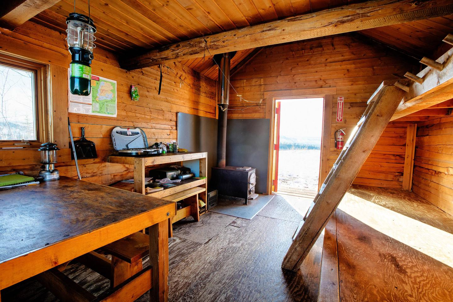 Inside of log cabin with view toward open front doorCache Mountain Cabin interior with bunks, cooking counter, and woodstove.