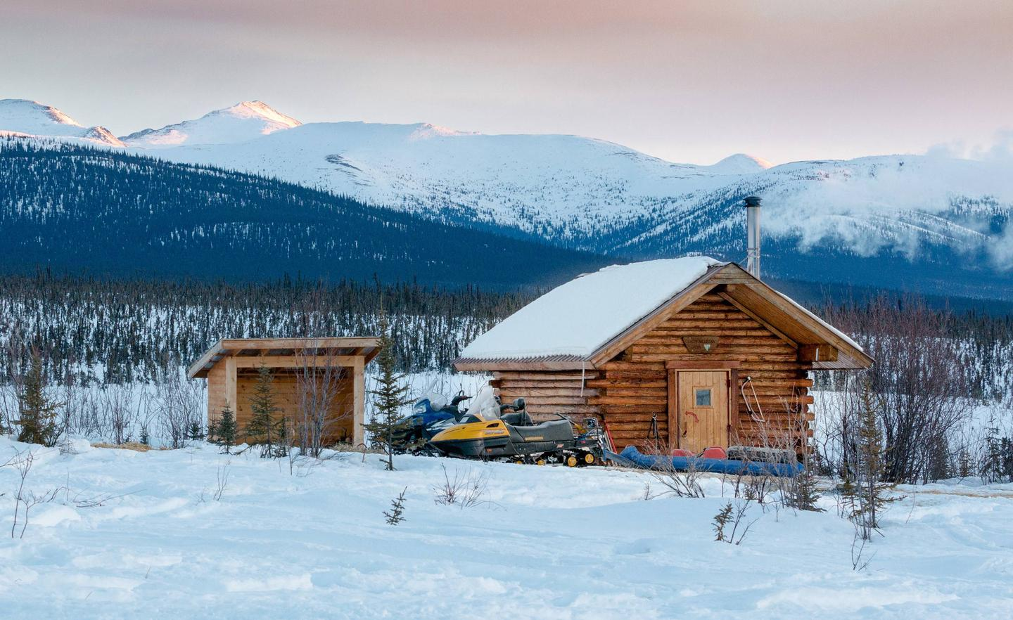 Log cabin and woodshed with mountainsEarly morning at Cache Mountain Cabin