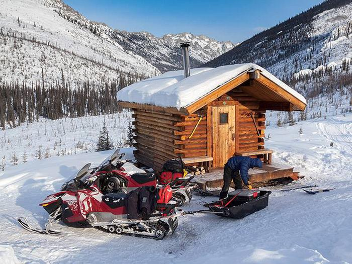 Man loads sled and snowmobiles in front of log cabinCaribou Bluff Cabin