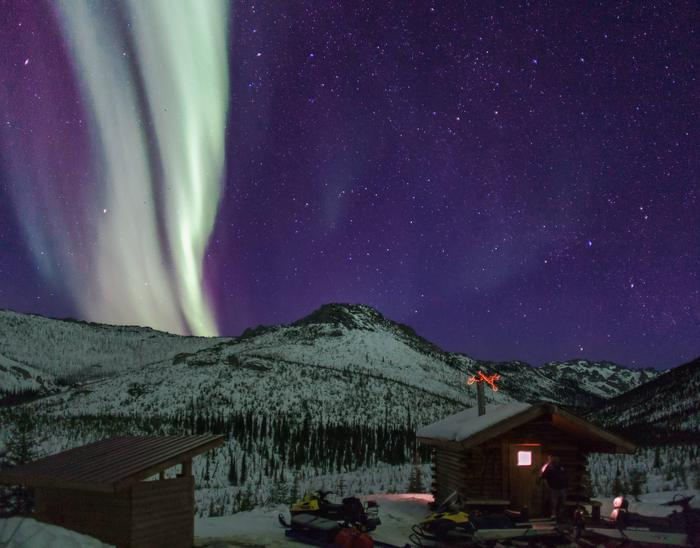Log cabin with mountains and northern lightsNorthern lights at Caribou Bluff Cabin