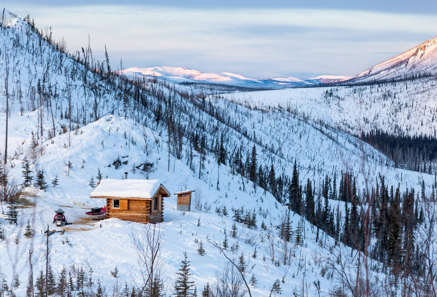 Cabin and snow-covered mountains at duskCaribou Bluff and Fossil Creek valley