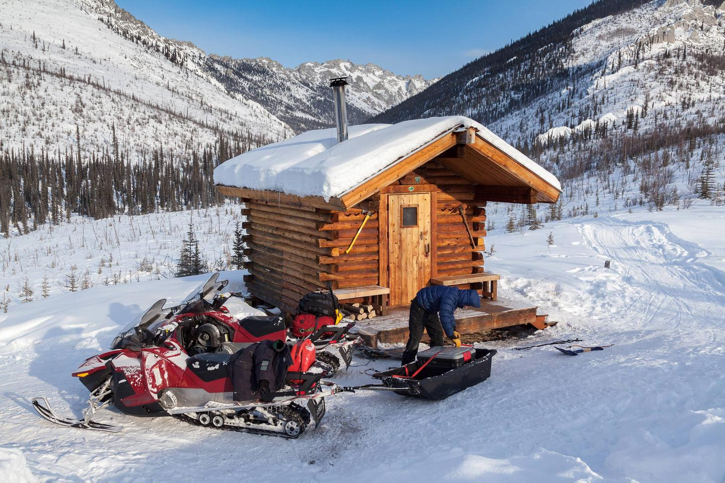 Man loads sled and snowmobiles in front of log cabinPreparing to depart from Caribou Bluff Cabin