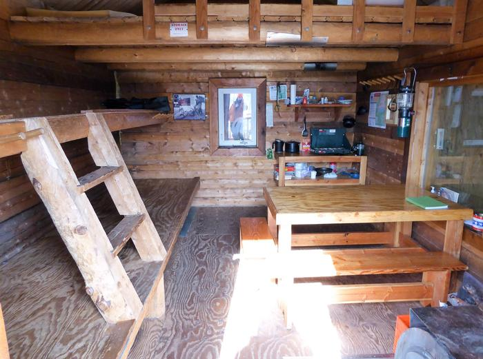 Inside of log cabin with bunks, table, and cooking counterInterior of Eleazar's Cabin