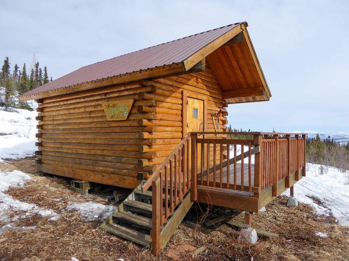 Log cabin on hillside partially covered in snowEleazar's Cabin in late winter
