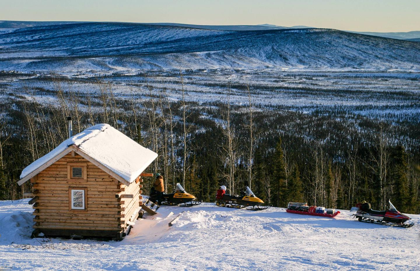 Cabin and parked snowmobiles on hillside above forestEleazar's Cabin overlooks the Wickersham Creek drainage and is accessible via a one-mile spur trail from the Wickersham Creek Trail.