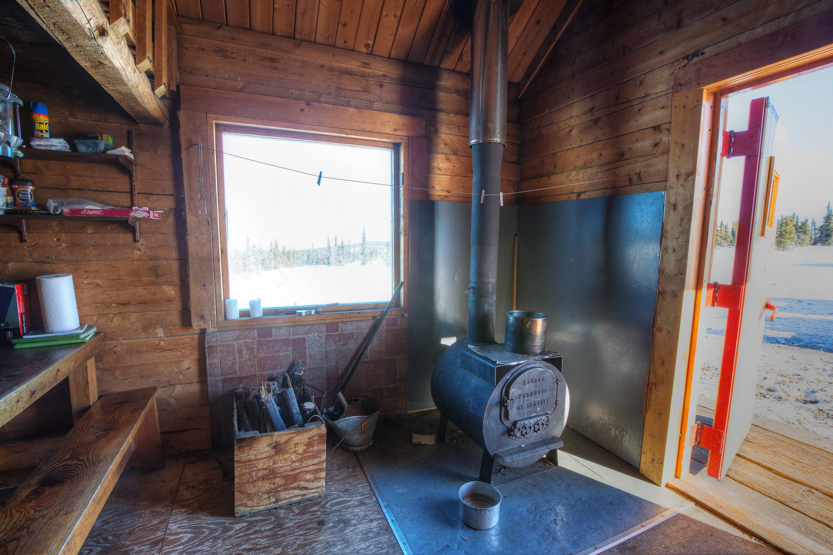 Inside view of log cabin with woodstove, window, and doorwayWoodstove and picture window at Lee's Cabin