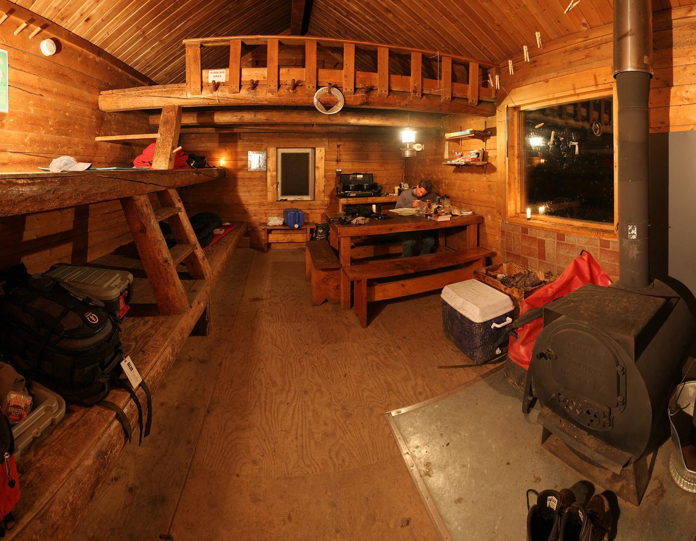 Log cabin interior with bunks, table, and woodstoveInterior of Lee's Cabin
