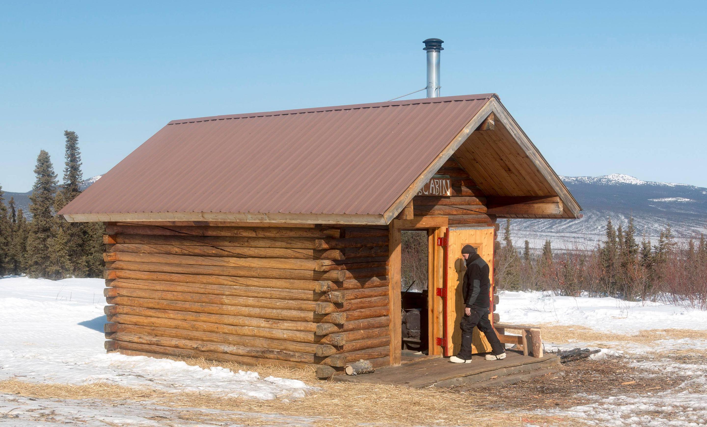 Man walks into a cabin in a snowy clearingLee's Cabin