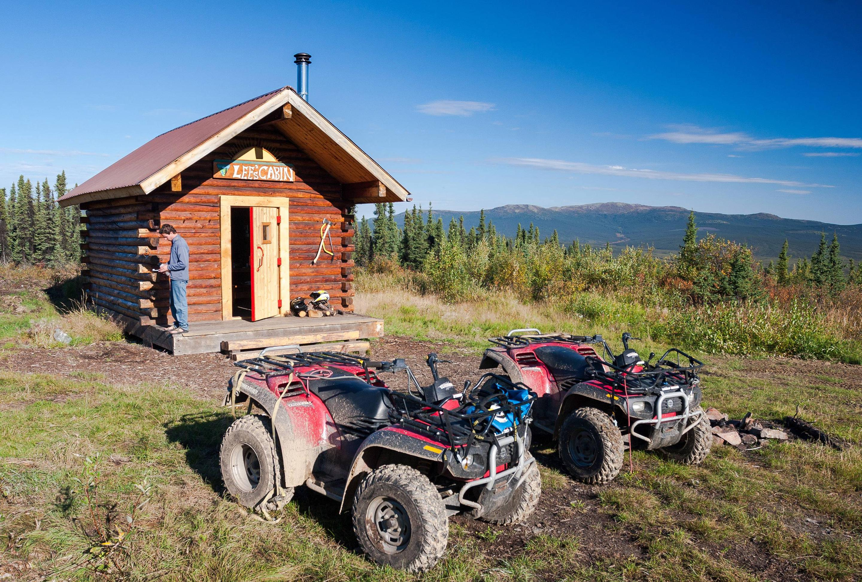 Two all-terrain vehicles parked in front of a log cabinLee's Cabin, unlike many of the White Mountains cabins, is readily accessible in summer.