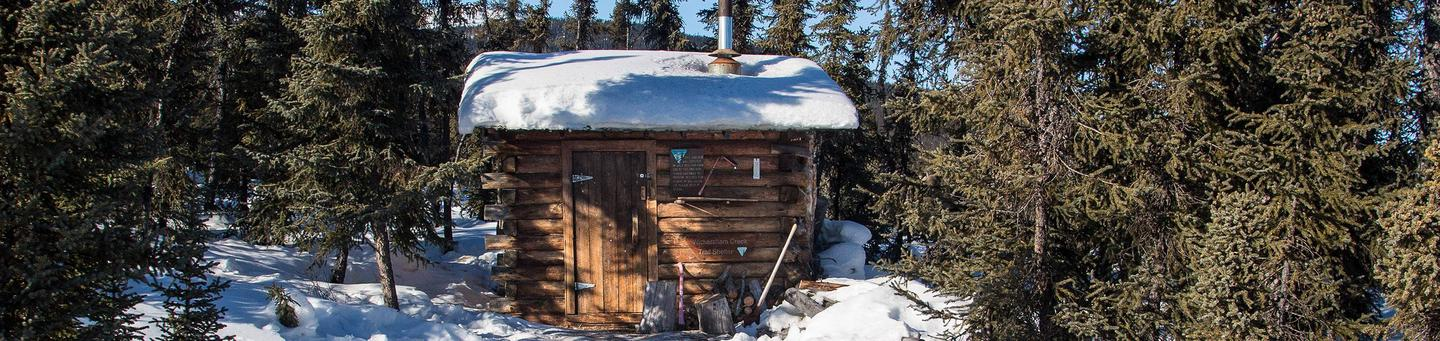 Small cabin with snowy roofWickersham Creek Trail Shelter
