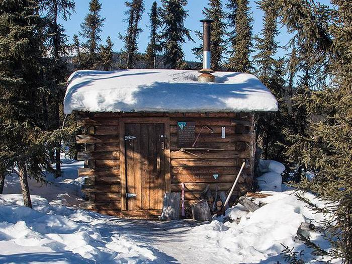 Log cabin with snow-covered roofWickersham Creek Trail Shelter