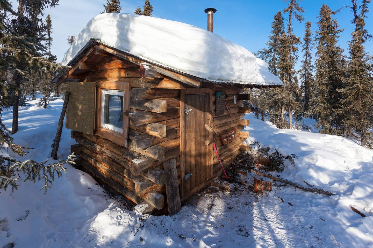 Side view of small cabin with snowy roofWickersham Creek Trail Shelter