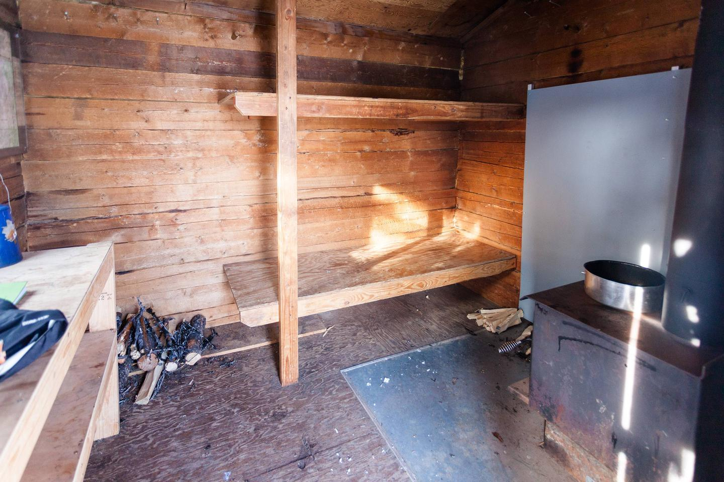 Inside view of very small log cabin with bunks and woodstoveInterior of Wickersham Creek Trail Shelter